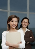 Businesswomen smiling at camera, focus on the foreground - Asia Images Group