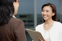 Female executive handing folders over to woman in front of her - Asia Images Group