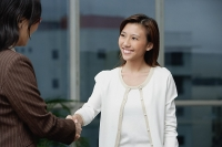 Businesswomen shaking hands - Asia Images Group