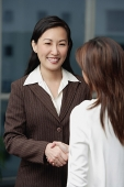 Two businesswomen shaking hands, over the shoulder view - Asia Images Group