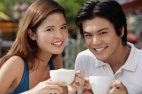 Couple in cafe having coffee, smiling at camera - Asia Images Group