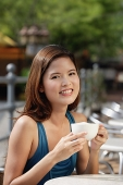 Woman having coffee in cafe, smiling at camera - Asia Images Group