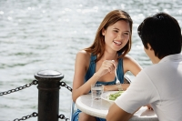 Couple sitting at outdoor cafe, having lunch - Asia Images Group