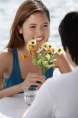 Couple sitting at outdoor cafe, woman holding flowers - Asia Images Group