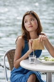Woman sitting at table in cafe, holding her purse - Asia Images Group
