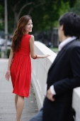 Woman looking over shoulder at man behind her - Asia Images Group