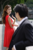 Woman waving at man in foreground - Asia Images Group