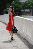 Woman in red dress carrying shopping bags, looking over shoulder - Asia Images Group