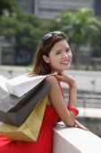 Woman carrying shopping bags over shoulder, leaning on railing - Asia Images Group