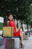 Woman sitting on park bench, shopping bags next to her - Asia Images Group