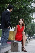 Woman on park bench, smiling at man standing next to her - Asia Images Group