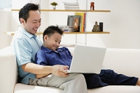 Father and son in living room, looking at laptop - Asia Images Group