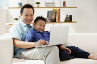 Father and son in living room with laptop, smiling at camera - Asia Images Group
