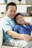 Father and son smiling at camera, portrait - Asia Images Group