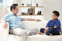 Father and son sitting on sofa, smiling at each other - Asia Images Group