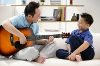 Father and son sitting on sofa, father playing guitar - Asia Images Group