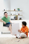 Father sitting on sofa, son on floor holding up drawing pad - Asia Images Group