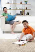 Father sitting on sofa, son on floor with drawing pad - Asia Images Group