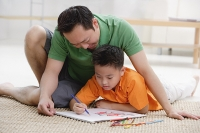 Father and son at home, drawing on sketchbook - Asia Images Group