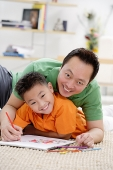 Father and son at home, lying on floor with sketch pad, smiling at camera - Asia Images Group