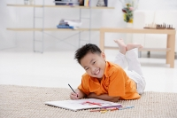 Boy lying on floor with sketch pad, smiling at camera - Asia Images Group