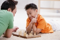 Father and son lying on floor, playing chess, smiling - Asia Images Group