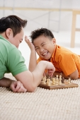 Father and son lying on floor, playing chess, son laughing - Asia Images Group