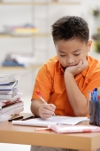 Boy sitting at desk, doing homework - Asia Images Group