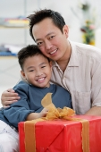Father and son next to gift box, looking at camera - Asia Images Group