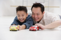 Father and son lying on floor, playing with toy cars - Asia Images Group