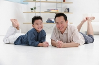 Father and son lying on floor, smiling at camera, portrait - Asia Images Group