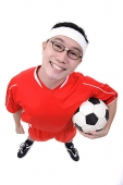 Man holding soccer ball under arm, looking at camera - Asia Images Group