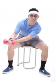 Man sitting on stool, using dumbbell - Asia Images Group
