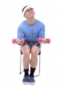 Man sitting on stool, lifting weights - Asia Images Group