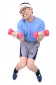 Man sitting on stool, lifting weights, grimacing - Asia Images Group