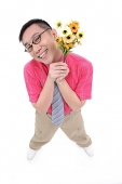 Man in shirt and tie holding flower bouquet, smiling at camera - Asia Images Group