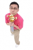 Man in shirt and tie holding flower bouquet, frowning - Asia Images Group