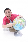 Man sitting on floor, pointing to globe, looking at camera - Asia Images Group