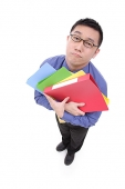 Businessman carrying  multi coloured folders, sad expression - Asia Images Group