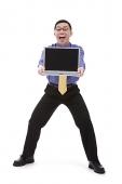 Businessman carrying laptop, portrait - Asia Images Group