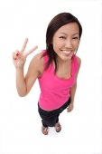 Young woman making peace sign, smiling up at camera - Asia Images Group