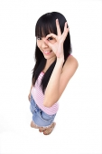 Young woman making OK sign, looking through fingers - Asia Images Group