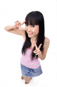 Young woman making peace sign, smiling - Asia Images Group