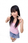 Young woman with fingers on cheek, smiling at camera - Asia Images Group