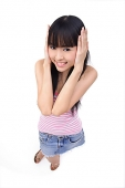 Young woman with hands over ears, looking at camera - Asia Images Group