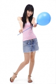 Young woman holding a blue balloon towards camera - Asia Images Group