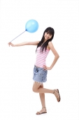Young woman holding a blue balloon, standing on one leg - Asia Images Group