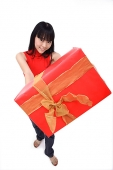 Young woman holding big red gift box towards camera - Asia Images Group