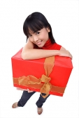 Young woman holding big red gift box, portrait - Asia Images Group