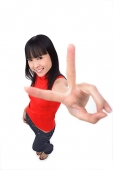 Young woman making peace sign at camera - Asia Images Group